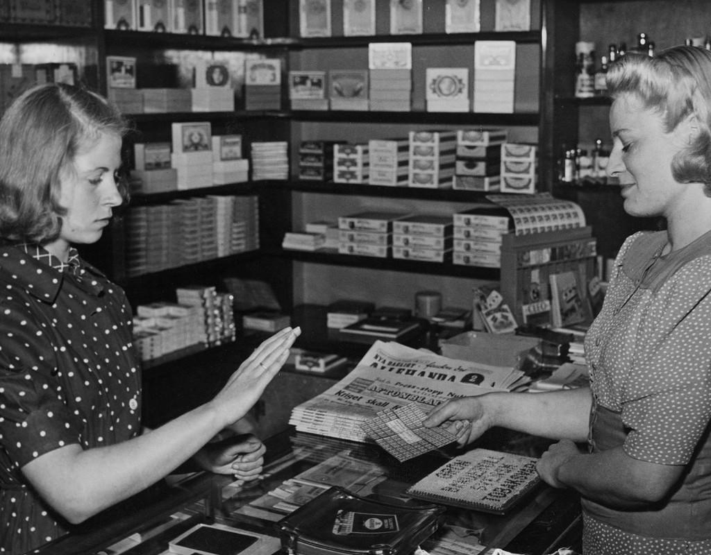 Kvinnor handlar med ransoneringskuponger i en butik på 40-talet.