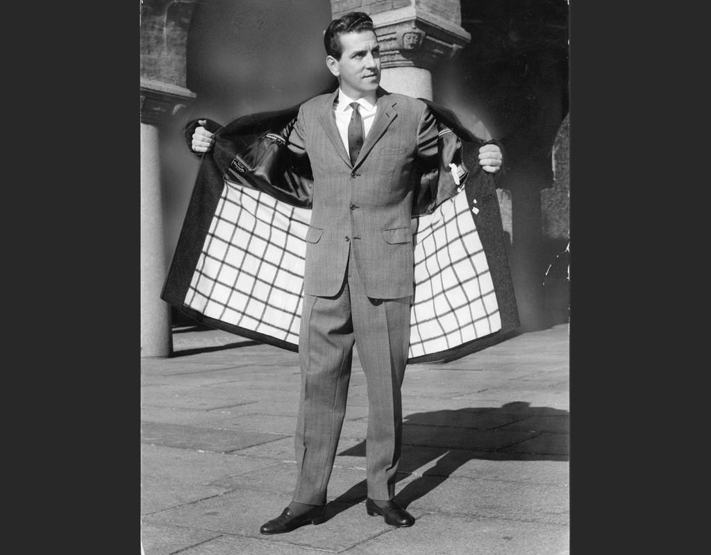 Männen, med vattenkammad sidbena, bär grå kostym i enkelt snitt med smal diskret slips, eller mer informellt skjorta och chinos.